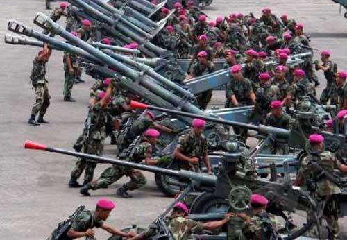 Prajurit artileri Marinir TNI AL sedang menyiapkan beberapa meriam, tampak M1939 K-61 pada bagian depan dengan ujung laras warna merah.